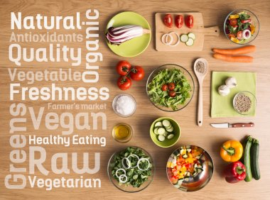 Creative vegetarian cooking at home with fresh healthy vegetables chopped, salads and kitchen wooden utensils, healthy eating text concepts on the left stock vector