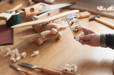 Man photographing his handmade wooden toy