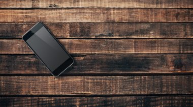Black mobile phone on a wooden table