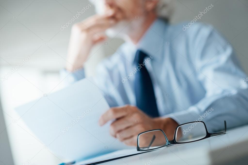 Pensive businessman reading a contract