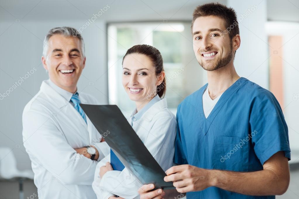 Medical team posing and examining an x-ray image