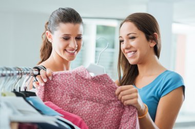 Cute young teen girlfriends shopping at the store and enjoying, one is holding a shirt stock vector