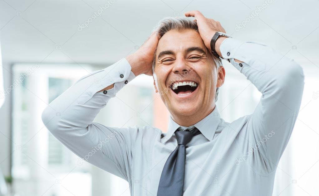 Cheerful careless businessman laughing and touching his forehead