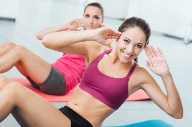 Smiling women exercising at the gym