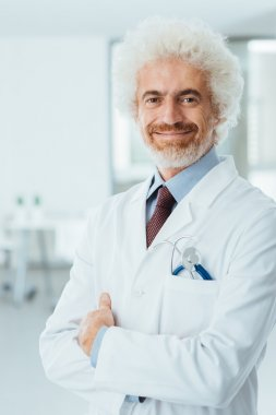 Confident doctor posing with folded arms