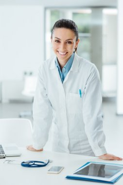 Confident female doctor leaning on desk