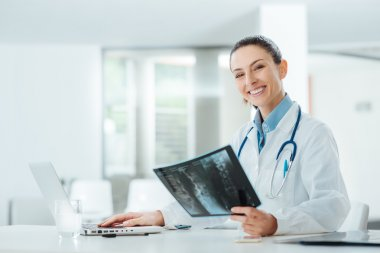 Smiling confident female doctor sitting at office desk and examining a patient's x-ray, she is looking at camera stock vector