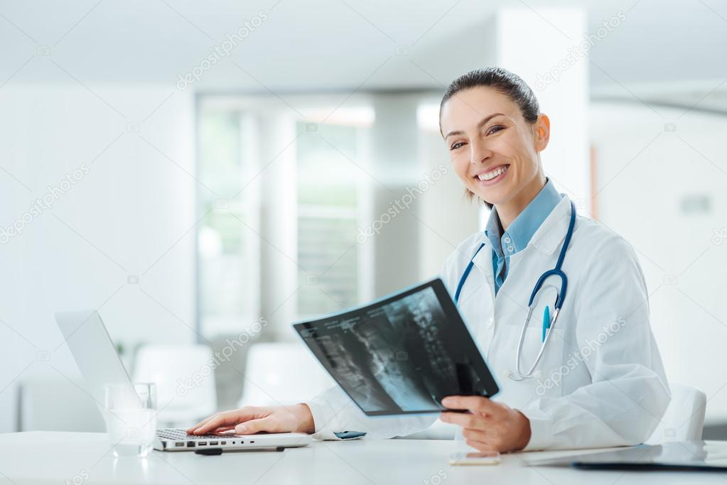 Smiling female doctor examining an x-ray