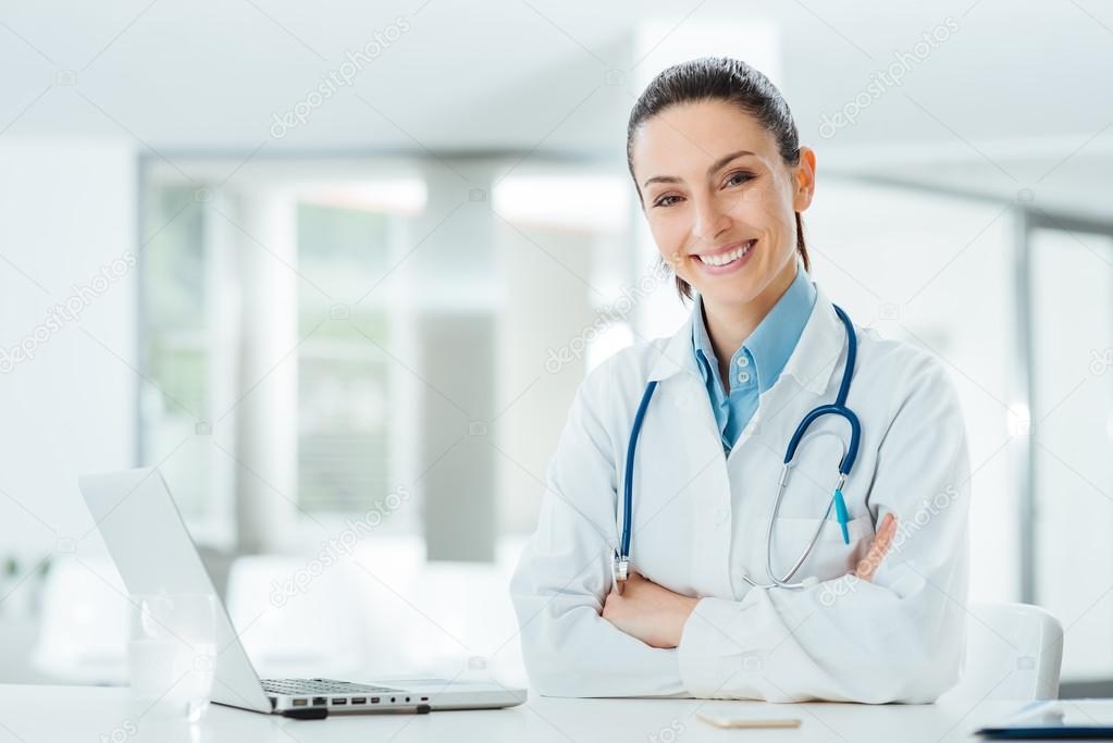 Confident female doctor at office desk