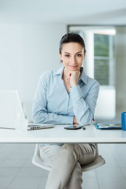 Confident female manager at desk posing
