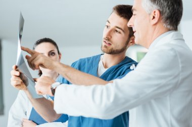 Professional medical team with doctors and surgeon examining patient's x-ray image, discussing and pointing stock vector
