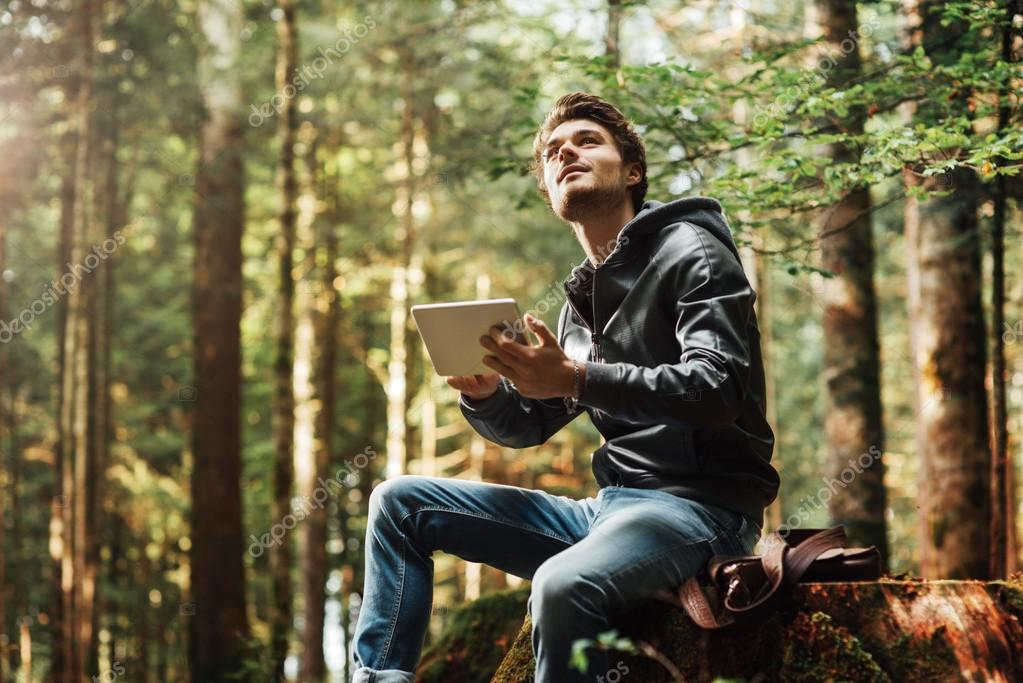 Young man using a digital tablet in the woods