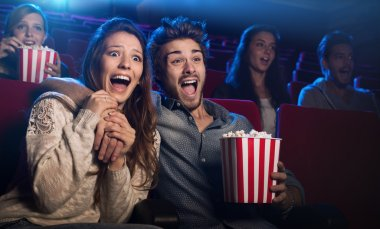 Young scared couple at the cinema watching an horror movie and screaming, she is holding her boyfriend's hand stock vector