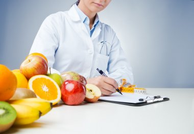 Professional nutritionist working at desk and writing medical records with fresh fruit on foreground stock vector