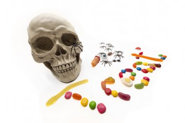 Skull with the word 'treat' spelled out in candy worms, beans and shapes. stock vector