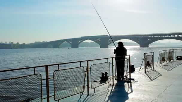 Silueta rybář hází rybářský prut