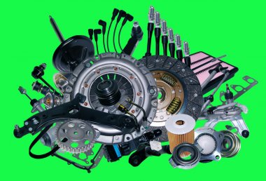 Many new spare parts for a car isolated on green background