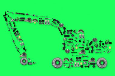 Many new spare parts in the form of excavator isolated on green background