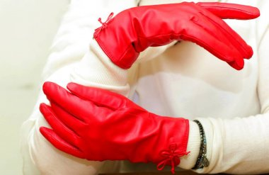 Hands in red leather gloves. Vintage leather gloves. Elegance and fancy look. Woman's hands wearing red reddish vintage gloves. Beauty and fashion.