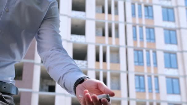 Muž hodí klíče od bytu do dlaně a pak je chytí druhou rukou, zblízka na pozadí domu ve výstavbě.