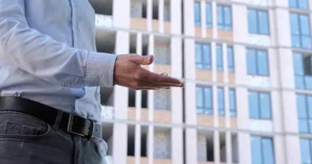 Ein Mann hält einen Schlüsselanhänger mit den Schlüsseln für die Wohnung in der Hand, dreht seine Handfläche und hält die Schlüssel mit den Fingern am Ring vor dem Hintergrund des Wohnhausbaus.