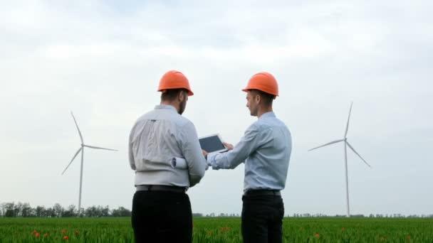 Dva pracovníci v pevných čepicích diskutují o výkonu větrných turbín pomocí indikátorů na tabletu.