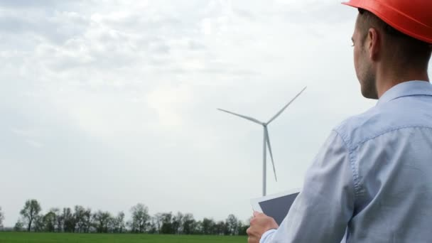 A man in a protective helmet with a tablet in his hands examines the working wind farms. Generation of environmentally friendly electricity out of wind.