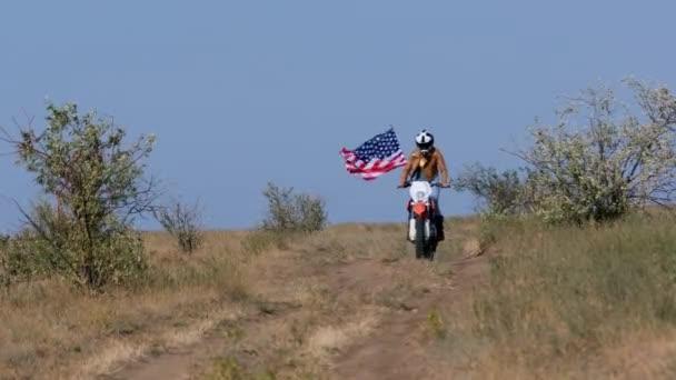 Žena jezdí na motorce s americkou vlajkou podél cross country
