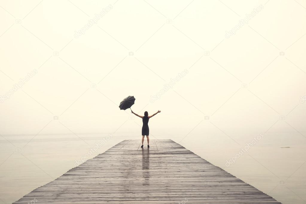 elegant woman in black rejoices with their arms up in the rain