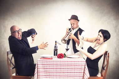 Angry couple disturbed by a trumpet musician while having dinner