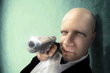 Freeze! Elegant killer pointing his gun
