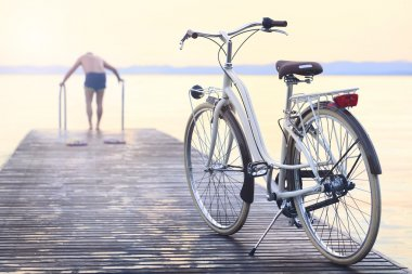 man parks bike on boardwalk befor jumping into the water