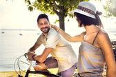 Coppie che hanno divertimento in bici in vacanza al lago