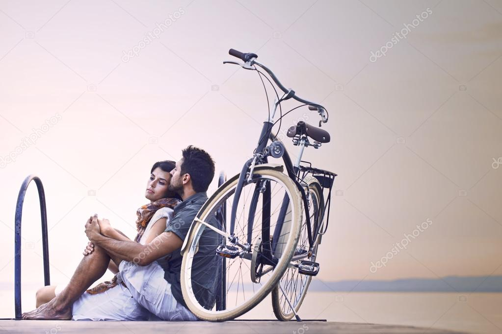 Couple in love resting on a boardwalk with a bike at the lake