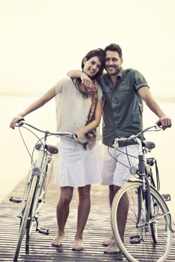 Couple in love pushing their bike toghether on a boardwalk