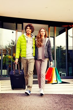 Couple with Shopping Bags and Suitcase