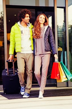 Young couple with luggage and shopping bags