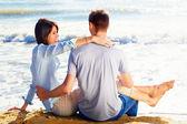 Coppie che si siedono sulla sabbia alla spiaggia guardando il mare