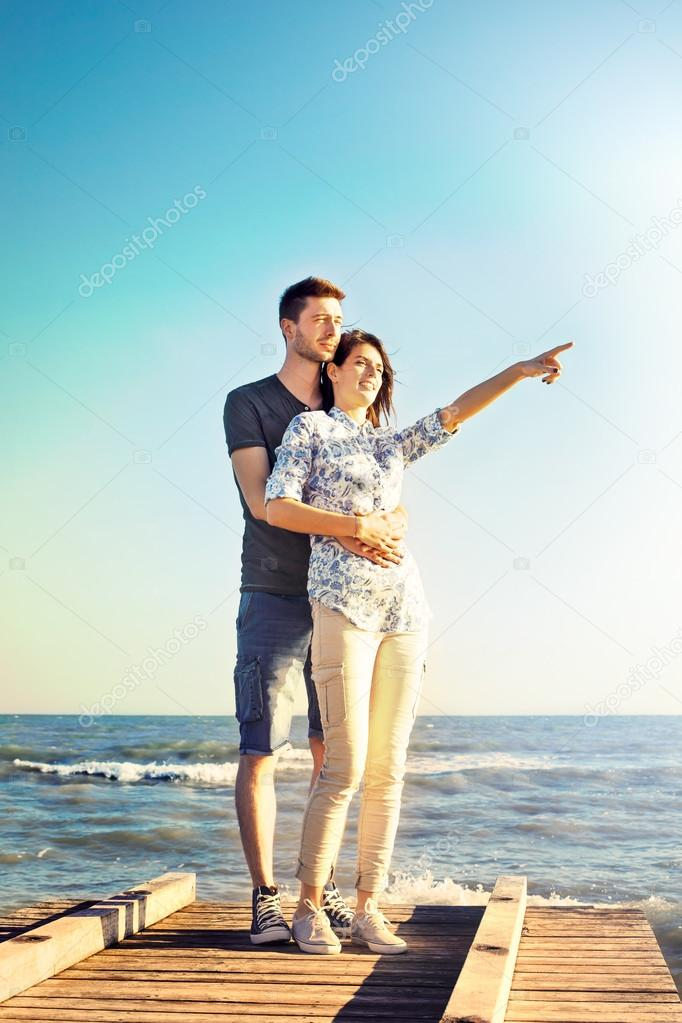Happy young couple standing pointing into the sky