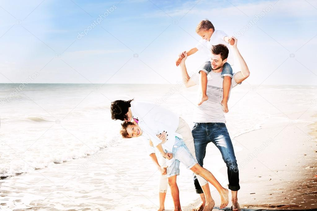 Family having fun on the beach to the sea