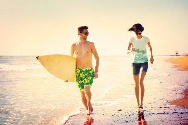 Surfers couple running on the seashore at sunset