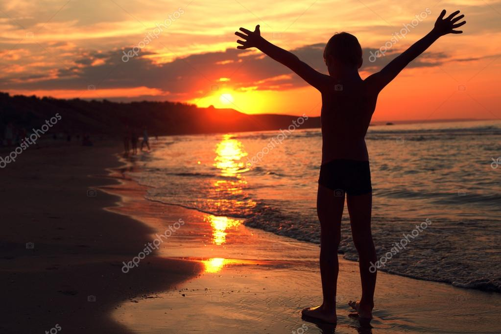Boy takes a deep breath at the fiery sunset on the sea