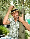 Farmář odpočívá vedle jeho olivové háje po arvesting oliv