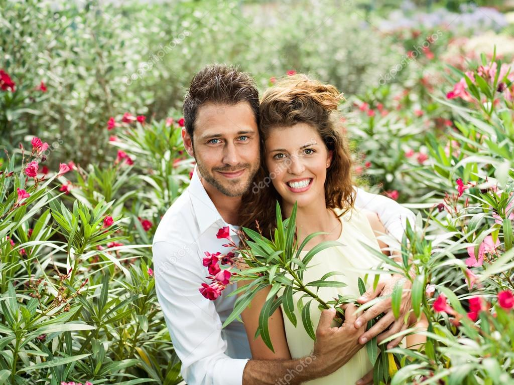 Couple flirting among the flowers in a greenhouse