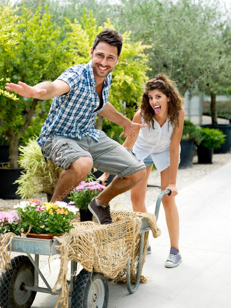 Young couple playing with a wheelbarrow in a greenhouse