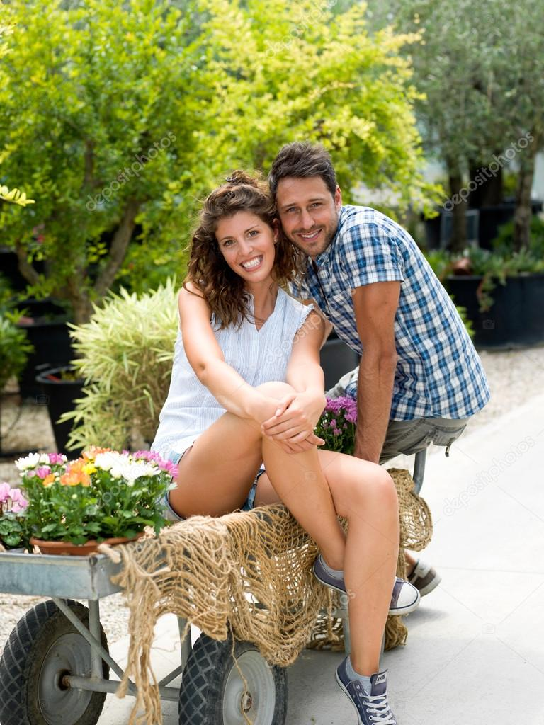 Young couple posing for a photo in a greenhouse