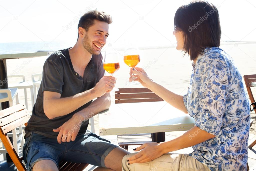 Happy couple drinking a spritz by the sea