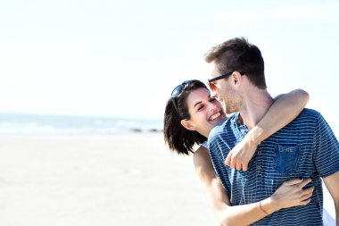 Couple in love hugging affectionately in front of the sea