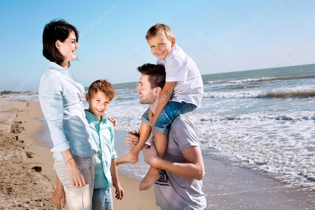 Happy family posing for a souvenir photo on the beach front of the sea