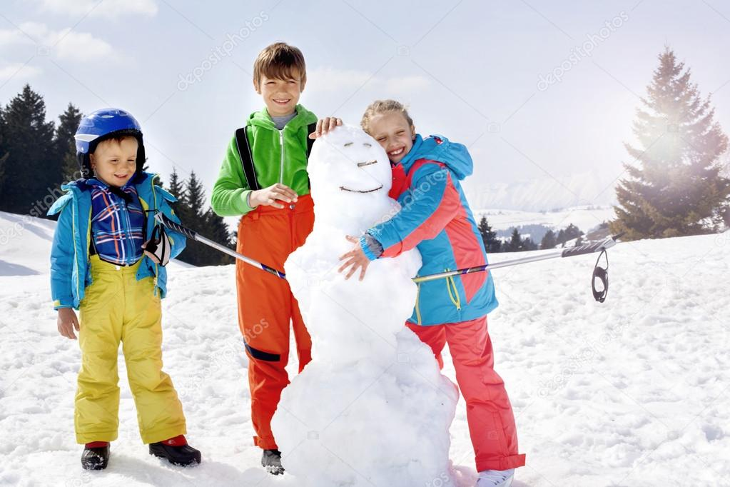 brothers and sister  building a snowman